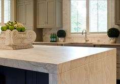 The fabulous waterfall edge island stone is Calacatta Gold marble which has been honed to a soft finish. Notice the precisely matched marble veining in the waterfall style countertop. Stunning!
