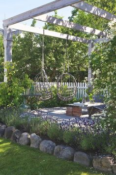 Schommelstoelen aan pergola in achterste deel tuin