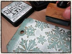By Tim Holtz. Ink inside top of embossing folder with Distress embossing ink (or VersaMark). Dry emboss kraft-core cardstock panel. Immediately apply white embossing powder. Rub powder off all raised designs. Randomly rub some off near top and bottom edges and in random spots all over. Heat emboss. Cool. Sand to expose kraft core around raised designs. Ink with Distress ink. (iced spruce used here). Distress edges of panel.