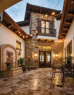 The cobblestone #courtyard is enhanced with potted plants, overhead strings of patio lights and the gentle sound of water. #housetrends