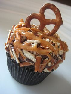 Chocolate caramel pretzel cupcake This website sells this delicious looking cupcakes. But I can see myself making a chocolate cupcake with fudge icing and adding broken pretzels and melted caramels and topping with a pretzel. Just Desserts, Delicious Desserts, Yummy Food, Tasty, Cupcake Recipes, Cupcake Cakes, Dessert Recipes, Cupcake Ideas, Think Food