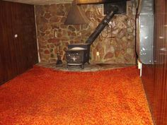 Shag carpeting. What is going on in this poor house? Totally 70's rock wall, carpeting, stove/fireplace, and wood paneling!