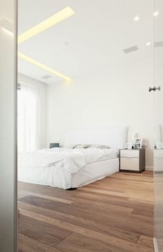White Bed With White Blanket And Pillows In Bright White Bedroom