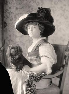 Antique photo of woman in a big hat with an adorable, little dog. I like the way she is looking right into the camera.