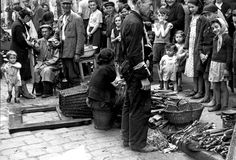 Warsaw Ghetto, Poland, Children standing around two people selling firewood.  The people in this photo did not survive. But were murdered by nazis