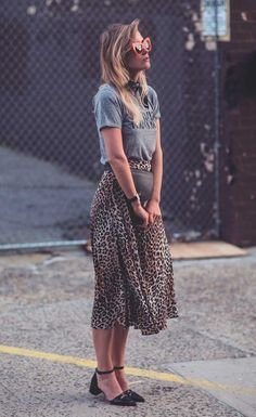 Street style look com camiseta e saia onça.