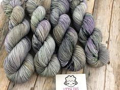 Under Wicked Sky is a moody speckled yarn with a medium grey base color, shots of lavender, green, plus hints of orange, with speckles of dark green and black over top. It reminds me of the sky before a nasty storm. Very Halloweeny and fun! Skeins can vary quite a bit within a dye lot,