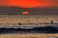 Sail boat and Surfers at Sunset in Oceanside. August 30, 2012