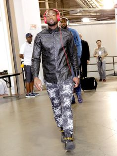 Dwayne Wade sports his game face in tie dye pants and shiny button down shirt.