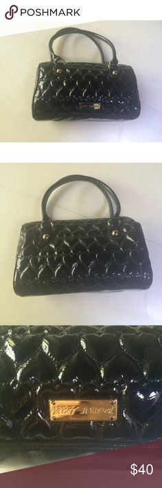 """Betsey Johnson black heart bag purse some satchel This is a very cute purse by Betsey Johnson. It has an adorable quilted heart pattern and is shiny like patent leather but is made of PVC. It is medium in size and has a zipper closure. Inside has a zipper pocket, key hook, and two open pockets for cell phone etc. Solid black. Lining is a logo print and 100% polyester. It has scratching on some hardware and some minor scuffs. See other listings for more photos.  Height: 8"""" Depth: 6"""" Length…"""