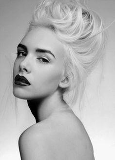 Platinum blonde hair, dark eyebrows, black lipstick. Nom.