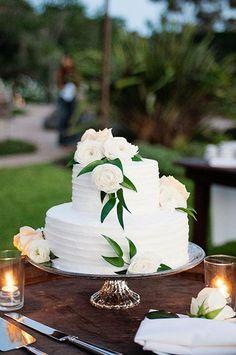 A two-tiered white wedding cake | @angiesilvy | Brides.com