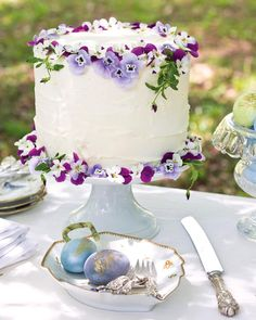 Edible pansies adorning a simple white cake elevate a classic dessert to a springtime showstopper. Find more inspiring décor ideas for your…