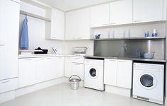 Na área molhada, sob a bancada de aço, ficam as máquinas de lavar e secar, além de espaço para roupas sujas. Ao lado, tábua de passar embutida e outros utensílios, como vassouras e produtos de limpeza