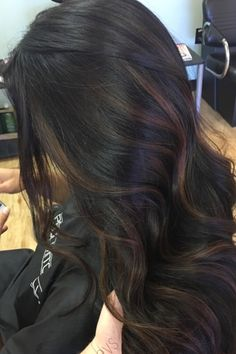 This models wavy dark brown hair is ever so lightly highlighted with some subtle, light brown highlights