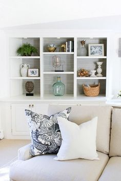 Built-in bookcases lined with grasscloth and simply styled