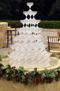 A tower of crystal champagne glasses waits to be filled on a low table decorated with leaves.