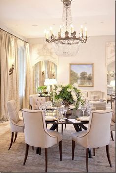 Elegance! The greenery & lovely painting provide a touch of color to this very pale room. The furniture, chandelier & detailing all contribute to making this a striking place!