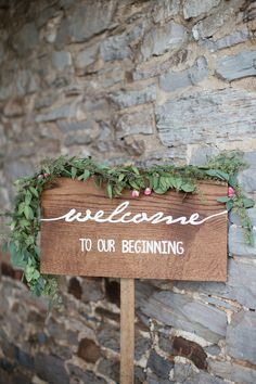 This signage welcoming guests to this couples ceremony with a delicate flower garland was the perfect simple detail.