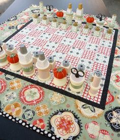 This is a very cool idea! A chess board quilt with sewing notion pieces. Love the little pin cushion queens!
