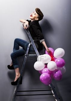 Pretty cheerful fashion retro model teen girl laughing on ladder in studio with balloons Stock Photo