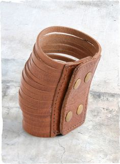 Our wide cuff is comprised of strips of cognac-hued leather, fastening with four brass snaps.