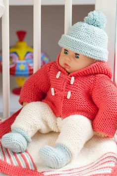 Knitted toggle coat, bobble hat, all-in-one, booties and striped blanket for a baby. Shop this knitting pattern now at The Knitting Network