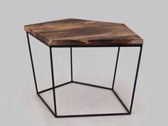 An interesting and original coffee table in geometric form..  The project has been used flamed top of pine wood on thin steel rods powder coated in a black structure. This gives the table unique, rustic character showing the unique grain of the wood . The effect is amazing and gives the interior a remarkable atmosphere.  dimensions: 80cm x 60cm x 45cm  Top is 3 cm thick brushed and burned pine wood.