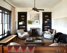 love the contrast of the dark bookshelves next to the white fireplace