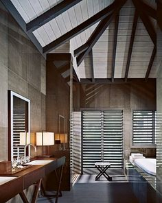 cliffside retreat on the Caribbean island of Antigua, of Giorgio Armani. A peaked beam ceiling contributes to the sense of spaciousness in a guest bath, which has walls made of wood laminate protected by sheets of glass. The shower stall has louvered doors that open to reveal the views. (November 2006)