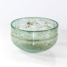 of pale blue glass, the vessel with vertical sides, the flat base with convex center, rounded rim, with small decorative ridge below the rim. Roman glass production developed during the Hellenistic pe