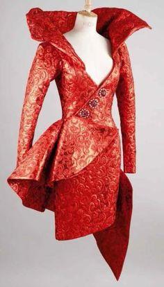 Yves SAINT LAURENT Haute couture n° 65759 Hiver 1989 Robe en broché lamé rouge à motifs de rinceaux, haut décolleté en pointe souligné d'une importante corolle baleinée, effet de boutonnage sur une ligne… - Gros & Delettrez - 14/10/2013