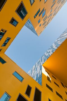 This angular structure looping around a central courtyard is an office building in Saint-Etienne by French studio Manuelle Gautrand Architectur  #yellow #france