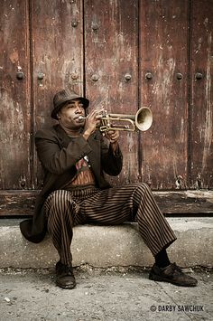 A trumpet player practices on a step in the old town of Havana, Cuba.