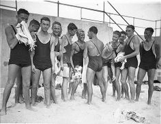 """Young male surfers tease Alf """"Bait"""" Gould about his backless swimsuit (a gift from his girlfriend), Bondi Beach, 10 Oc..."""