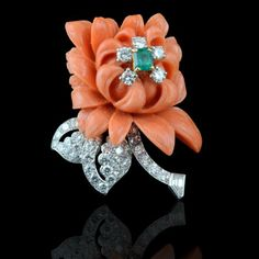 Striking coral, diamond and emerald brooch,  depicting a carved coral chrysanthemum, the petals with brilliant cut diamond details, mounted in platinum and 18ct gold by Cartier, Paris c.1950's