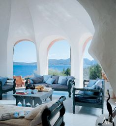 On Sardinia's Costa Smeralda, interior designer Florence Pucci expanded and decorated a villa originally built by architect Savin Couëlle. Pucci whitewashed the walls of the cavernous living room and chose pale-blue furnishings to give it an airy feeling. A terrace was added outside the arched windows, creating space beneath for new bedrooms and baths. (August 2008)  Photo: Durston Saylor