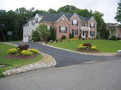 screaming color when a home is a place to rest.  Need structure and vertical to frame homeLandscaped Driveway Entrance