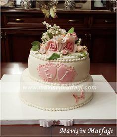 Şeker hamurundan çiçeklerle bezenmiş, iki katlı nişan pastası... Pastanın rahat servis edilebilmesi için, çiçeklerin olduğu üst kısım, şeker hamurundan hazırlanmış plaka üzerine yerleştirilmiştir.