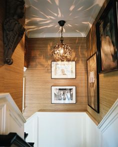 Framed art in a hallway with grass-cloth wallpaper