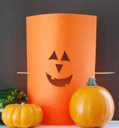 Easy peasy Halloween decoration. Cut out some shapes from paper to look like a face, stick a chopstick through the back, put a candle behind it and waa laa...instant Halloween decor.