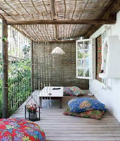 Suspensa em toras de eucalipto, a cobertura da varanda é de telhas de plástico transparente com bambu trançado, que também forma o painel na lateral. Os pufes de chita têm tudo a ver com o clima de praia