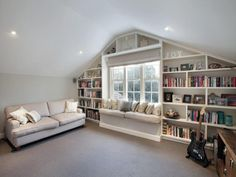 The built in bookshelves and bench along the wall with windows.