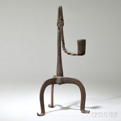 Wrought Iron Rushlight, England or America, late 18th/early 19th century, pivoting-jaw rushlight with candleholder counterweight on iron shaft extending to tripod base with pointed, upturned feet, ht. 11 1/4 in.