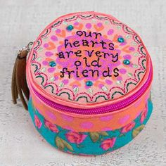 "Our Hearts are Very Old Friends Jewelry Round - This Jewelry round is emboidered on the top with ""Our hearts are very old friends"" and is embellished with rhinestones. The inside is lined and features a zippered closure. Roomy satin interior is large enough to store big jewelry pieces and keep your treasures safe"
