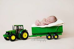 Newborn picture with a John Deere model tractor just like daddy's. This is perfect!  Wish i would have been taking pictures when jordy was a baby!