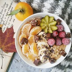 pearsnpancakes a bowl with yummy cinnamon oatmeal with looots of fruuuit on top including a gold kiwi plus cashew butter 'n cacao bar chunks