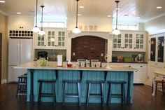 I love that island... awesome color pop in a white kitchen.