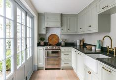 Light gray-green cottage kitchen displays brilliant natural light from sliding window cottage doors creating a cheerful and fresh look accented with brass hardware.