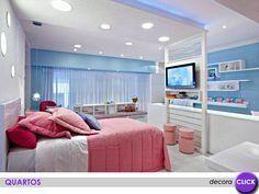Quarto de menina com móveis brancos e vários detalhes em cor-de-rosa e azul. Uma ideia para quartos grandes, quando a tv fica muito distante da cama, pode ser usado um painel como este para separar os ambientes, atrás dele fica a bancada de estudos.